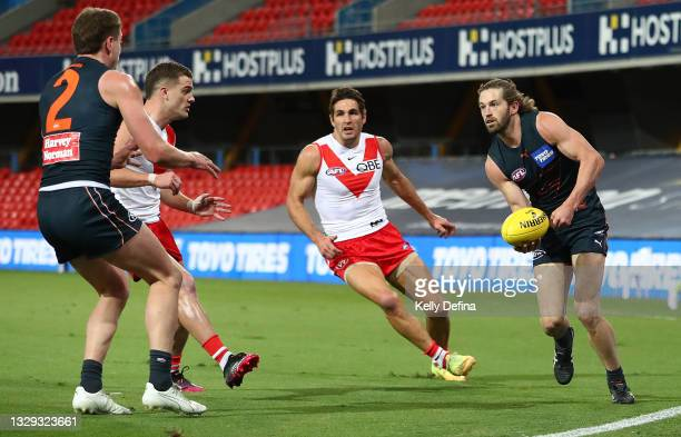 Callan Ward of the GWS Giants handballs during the round 18 AFL match between Greater Western Sydney Giants and Sydney Swans at Metricon Stadium on...