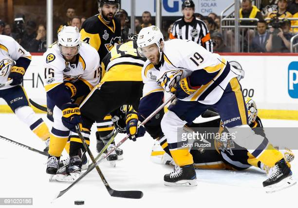 Calle Jarnkrok and Craig Smith of the Nashville Predators reach for the puck against the Pittsburgh Penguins during the first period of Game Two of...