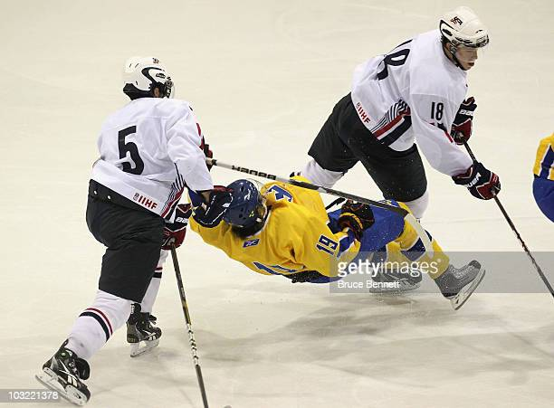 Calle Jarnkrok of Team Sweden is hit by Kyle Palmieri and John Norman of Team USA at the USA Hockey National Evaluation Camp game on August 3, 2010...