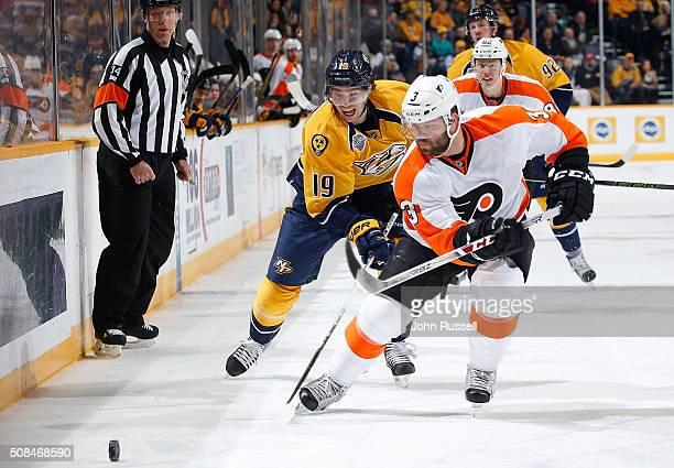 Calle Jarnkrok of the Nashville Predators skates for the puck against Radko Gudas of the Philadelphia Flyers during an NHL game at Bridgestone Arena...