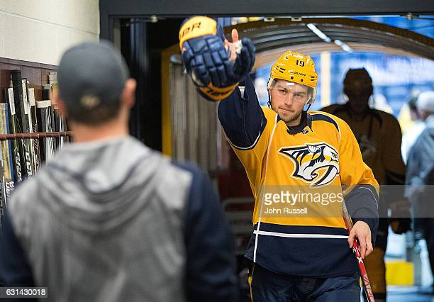 Calle Jarnkrok of the Nashville Predators tosses his gloves for the dryer after warmups prior to an NHL game against the Vancouver Canucks at...
