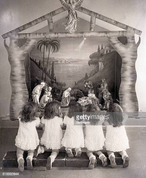12/1936 Callender Ontario In December the Quints learned the story of Christmas with the help of a creche Here wearing their best frocks they kneel...