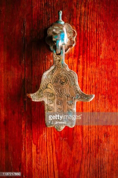 caller on door of hand of fatima - hand of fatima stock photos and pictures