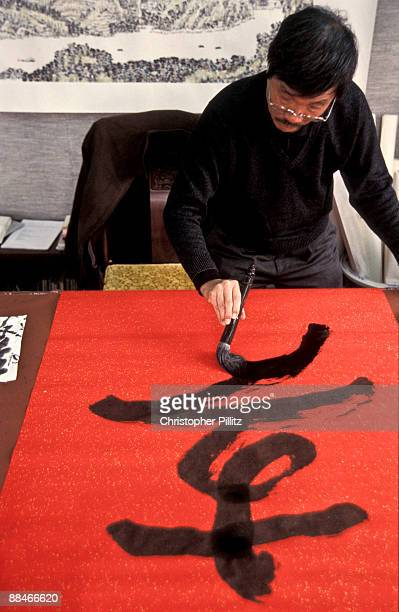 Calligrapher at work on a large red paper canvas
