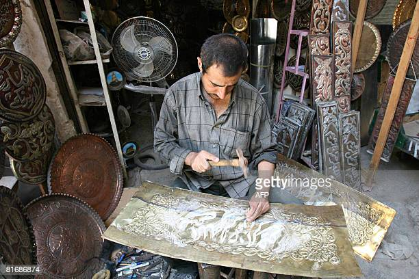 A calligrapher carves out religious script on a sheet of copper alloy to be made into a wall decoration at a workshop in a metalworking district of...