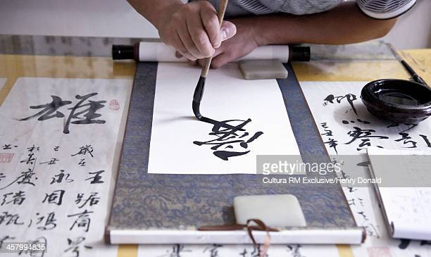 Calligrapher writing Chinese symbols on scroll