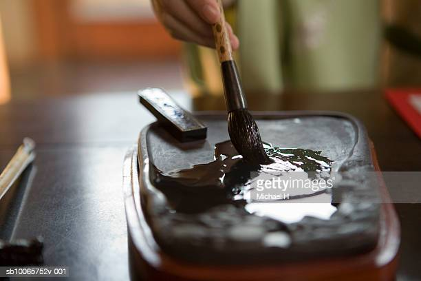 Calligraphy brush being dipped into ink stone