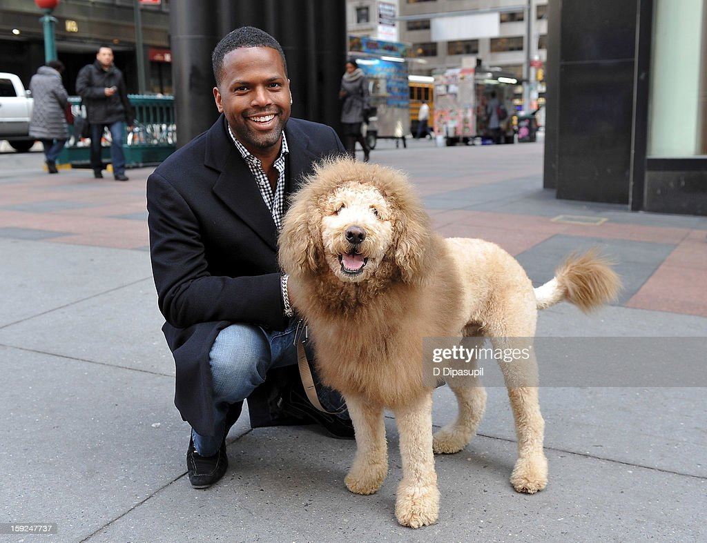 AJ Calloway poses with Charles the Monarch during a taping of 'Extra' in Times Square on January 10, 2013 in New York City.
