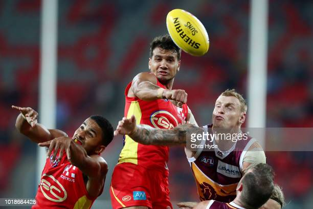 Callum Ah Chee of the Suns and Mitch Robinson of the Lions compete for the ball during the round 22 AFL match between the Gold Coast Suns and...