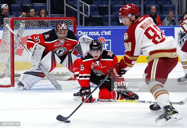 Callum Booth of the Quebec Remparts eyes the puck as Antoine Morand of the Acadie-Bathurst Titan prepares to shoot during their QMJHL hockey game at...