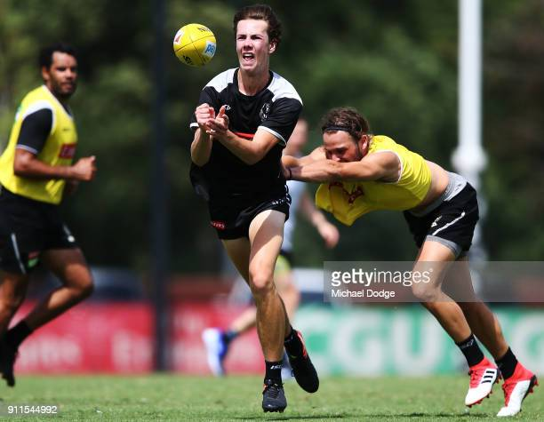Callum Brown handballs away from Tim Broomhead during a Collingwood Magpies AFL training session on January 29 2018 in Melbourne Australia
