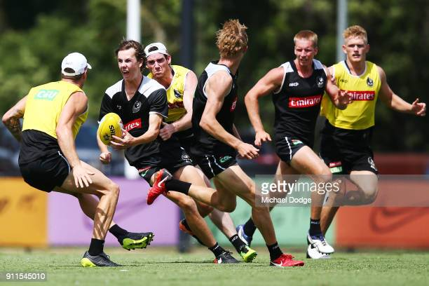 Callum Brown handballs away from Tyson Goldsack during a Collingwood Magpies AFL training session on January 29 2018 in Melbourne Australia
