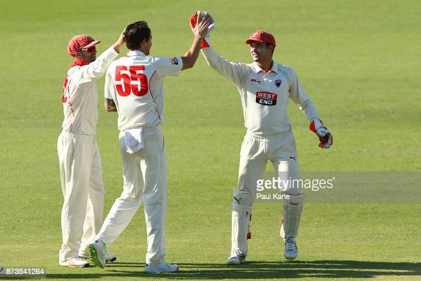 Callum Ferguson and Alex Carey of South Australia congratulate Kane Richardson after dismissing Marcus Stoinis of Western Australia during day one of...