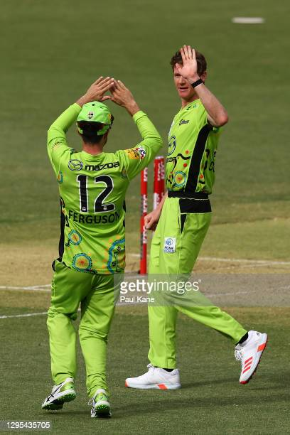 Callum Ferguson and Brendan Doggett of the Thunder celebrate the wicket of Josh Inglis of the Scorchers during the Big Bash League match between the...