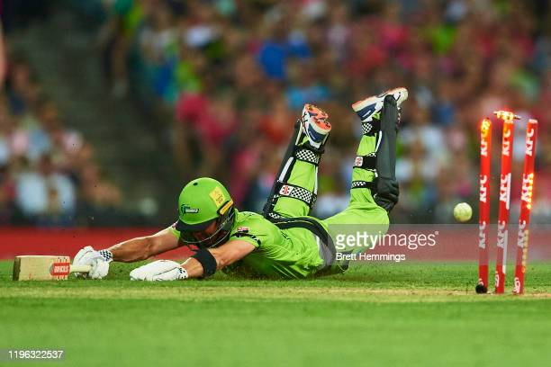 Callum Ferguson of the Thunder is run out by Josh Philippe of the Sixers during the Big Bash League match between the Sydney Sixers and the Sydney...
