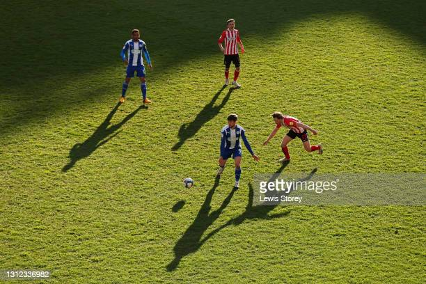 Callum Lang of Wigan Athletic battles for possession with Denver Hume of Sunderland during the Sky Bet League One match between Wigan Athletic and...