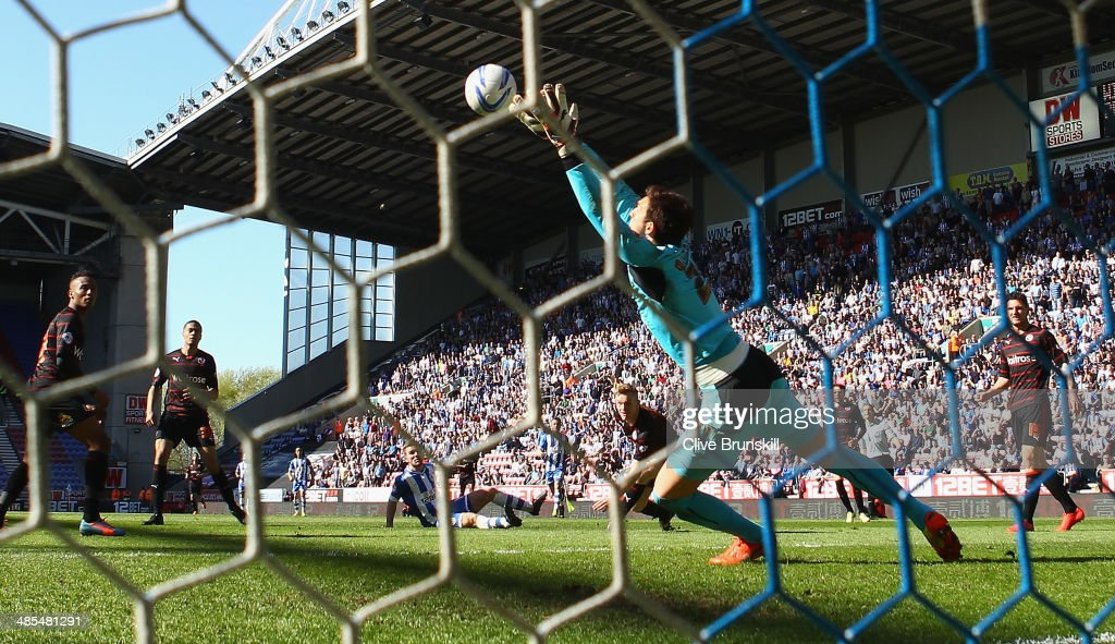 Callum McManaman of Wigan Athletic scores his teams third goal past Reading keeper Alex McCarthy during the Sky Bet Championship match between Wigan Athletic and Reading at DW Stadium on April 18, 2014 in Wigan, England.
