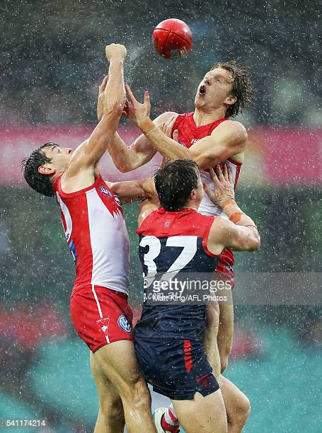 Callum Mills of the Swans and Nick Smith of the Swans are challenged by Aaron Vandenberg of the Demons during the round 13 AFL match between the...