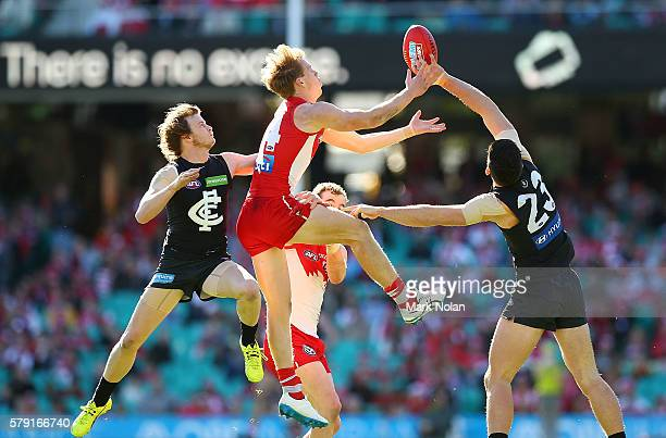 Callum MIlls of the Swans contest a mark with Liam Sumner and Jacob Weiterging of Carlton during the round 18 AFL match between the Sydney Swans and...