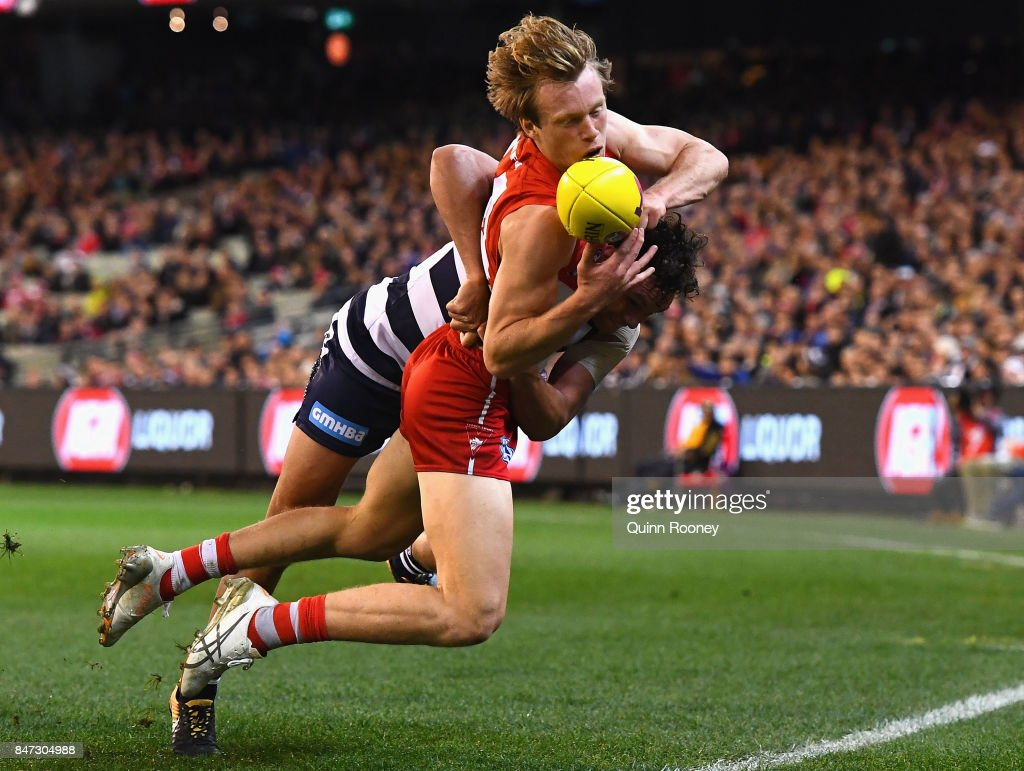 Callum Mills of the Swans handballs whilst being tackled by Steven Motlop of the Cats during the Second Semi Final AFL match between the Geelong Cats and the Sydney Swans at Melbourne Cricket Ground on September 15, 2017 in Melbourne, Australia.
