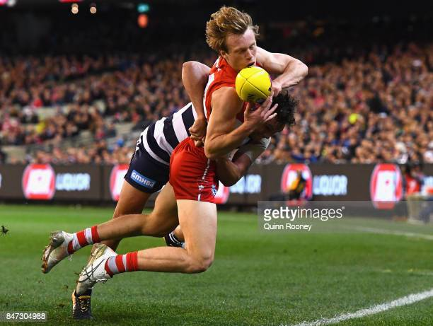 Callum Mills of the Swans handballs whilst being tackled by Steven Motlop of the Cats during the Second Semi Final AFL match between the Geelong Cats...