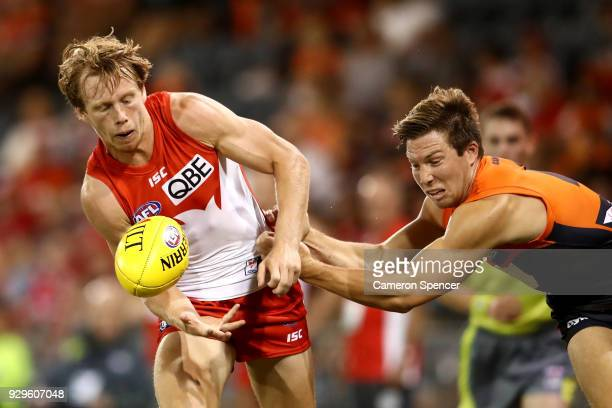 Callum Mills of the Swans is tackled by Toby Greene of the Giants during the JLT Community Series AFL match between the Sydney Swans and the Greater...