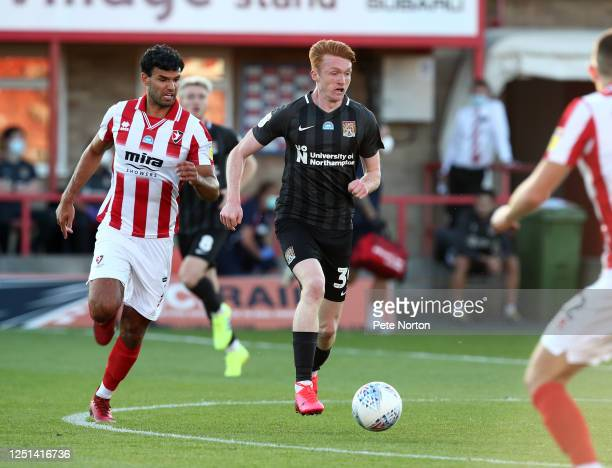 Callum Morton of Northampton Town moves forward with the ball away from Conor Thomas of Cheltenham Town during the Sky Bet League Two Play Off...