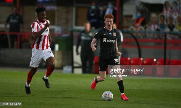 Callum Morton of Northampton Town moves forward with the ball away from Rohan Ince of Cheltenham Town during the Sky Bet League Two Play Off...