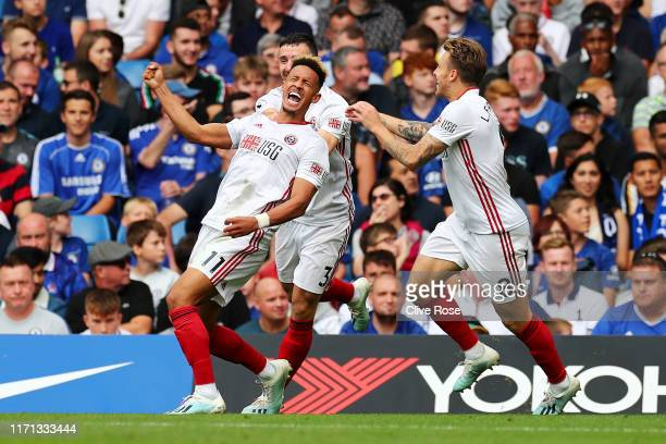 Callum Robinson of Sheffield United celebrates with teammates after scoring his team's first goal during the Premier League match between Chelsea FC...