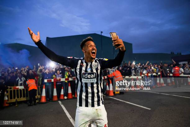 Callum Robinson of West Bromwich Albion celebrates with the fans outside as promotion to the Premier League is confirmed on the final day during the...