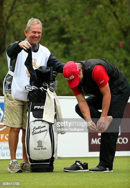 Callum Shinkwin of England adjusts a plaster on his toe on the 11th as his caddie Dave McNeilly holds his sock during the first round of the Trophee...