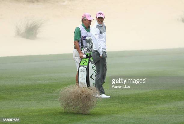 Callum Shinkwin of England laugh as a tumbleweed crosses the eighth fairway during the second round of the Omega Dubai Desert Classic on the Majils...