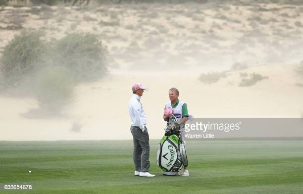 Callum Shinkwin of England stands with his caddie Dave McNeilly as winds blow sand across the course during the second round of the Omega Dubai...
