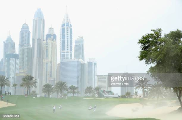 Callum Shinkwin of England turns his back as strong winds blow sand across the eighth fairway during the second round of the Omega Dubai Desert...