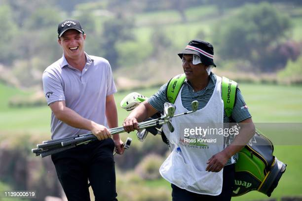 Callum Shinkwin on England assists his caddie by carrying clubs up the hill on the 17th during round two of the Hero Indian Open at the DLF Golf &...