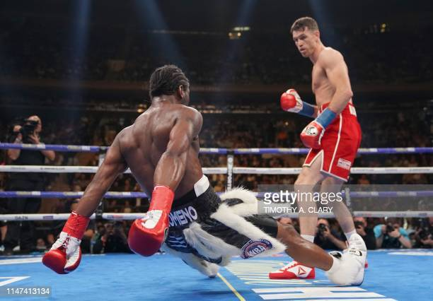 Callum Smith of England knocks down Hassan N'Dam N'Jikam of Monaco during their WBA and WBC Championship fight at Madison Square Garden in New York...