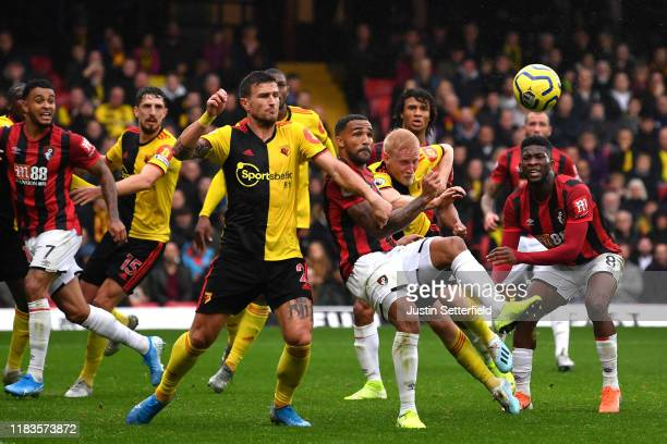 Callum Wilson of AFC Bournemouth battles for possession with Will Hughes of Watford during the Premier League match between Watford FC and AFC...