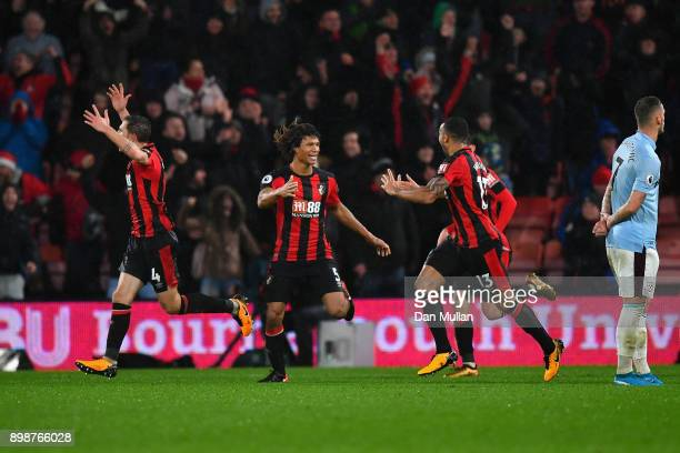 Callum Wilson of AFC Bournemouth celebrates with team mates Nathan Ake and Dan Gosling after scoring their sides third goal during the Premier League...