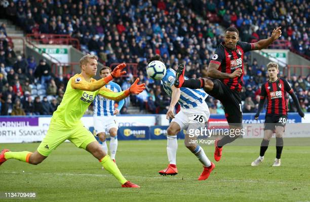 Callum Wilson of AFC Bournemouth chases Jonas Lossl of Huddersfield Town for the ball during the Premier League match between Huddersfield Town and...