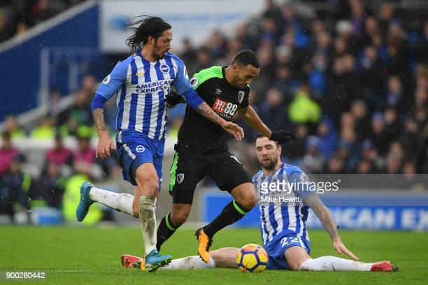 Callum Wilson of Bournemouth is tackled by Matias Ezequiel Schelotto and Shane Duffy of Brighton during the Premier League match between Brighton and...