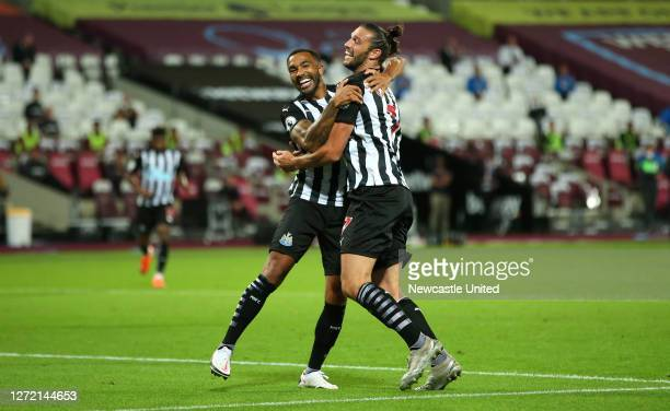 Callum Wilson of Newcastle United celebrates with teammate Andy Carroll after scoring his team's first goal during the Premier League match between...