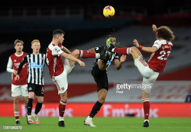 Callum Wilson of Newcastle United is challenged by Granit Xhaka of Arsenal and David Luiz of Arsenal during the Premier League match between Arsenal...