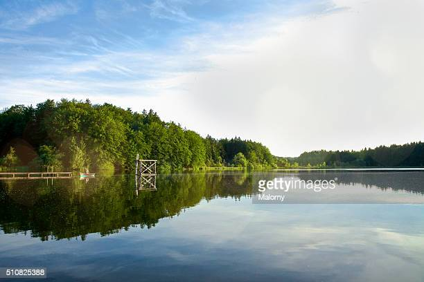 calm and beautiful lake with diving platform and single rowing boat. griessee, bavaria, germany - lago - fotografias e filmes do acervo