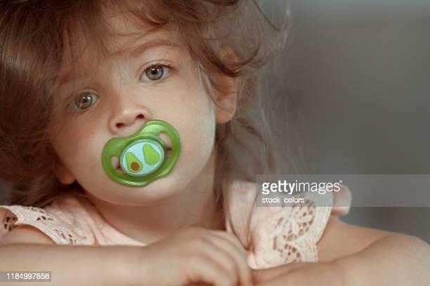 kalm baby meisje met fopspeen - 2 3 jaar stockfoto's en -beelden