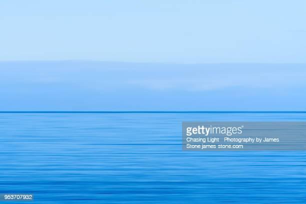 calm blue sea leading to blue sky at horizon - paysage marin photos et images de collection
