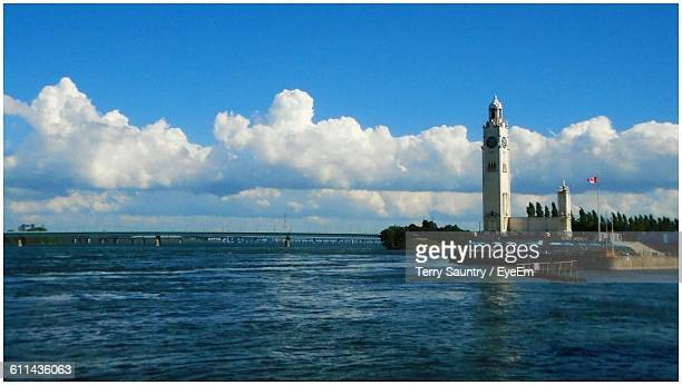Calm Blue Sea With Lighthouse In Distance Against Sky