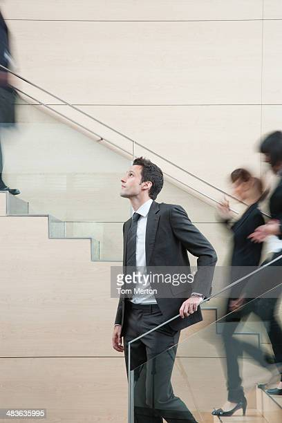 calm businessman in busy office staircase - lingering bildbanksfoton och bilder