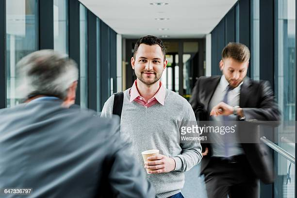 Calm businessman in contrast to businessmen in a hustle