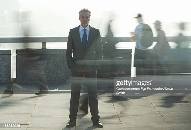 Calm businessman on street with people rushing by