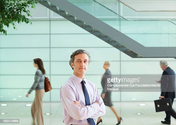 Calm businessman standing in busy lobby